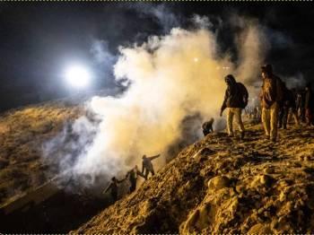 Pendatang Amerika Tengah yang cuba menyeberang sempadan dari Tijuana ke San Diego melarikan diri daripada terkena gas pemedih mata yang dilepaskan pengawal sempadan AS. - Foto AFP