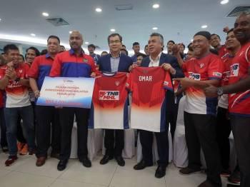 Pengurus Besar (Hal Ehwal Korporat) Tenaga Nasional Berhad (TNB), Datuk Omar Sidek (tiga, kanan) sewaktu penyerahan replika cek penajaan berjumlah RM 4 juta kepada Konfederasi Hoki Malaysia (MHC) yang diwakili oleh Bendahari MHC, Selvendran Saravanamuthu (empat, kiri) serta pengenalan jersi baharu Pasukan Hoki TNB dan TNB Thunderbolts pada Majlis Penyerahan Tajaan TNB Kepada MHC dan sesi memperkenalkan Pasukan Hoki TNB dan TNB Thunderbolts sempena TNB-Liga Hoki Malaysia 2019 di Padang Kelab Kilat TNB Bangsar, hari ini. - Foto Bernama