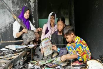 Nurin Emiliyana Tasha (dua,kanan) bersama kakak dan adiknya serta ibu sedang melihat buku sekolah mereka yang musnah.