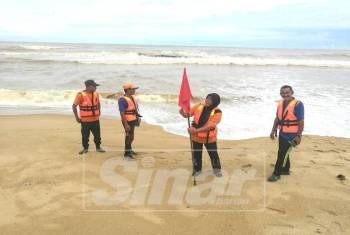 Penyelamat Pantai APM memacak bendera merah  sebagai peringatan kepada pengunjung jangan menghampiri pantai.