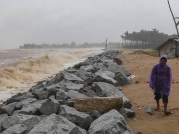 Penduduk tempatan meninjau keadaan ombak dan laut yang bergelora di benteng pemecah ombak berhampiran kediaman di Pantai Pulau Kundur. - Foto Bernama
