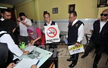 Seorang pengusaha kedai makan menandatangani notis amaran dan diperhatikan Chee Leong keranan gagal mempamerkan tanda larangan merokok di Hang Tuah Mall, di sini, hari ini.