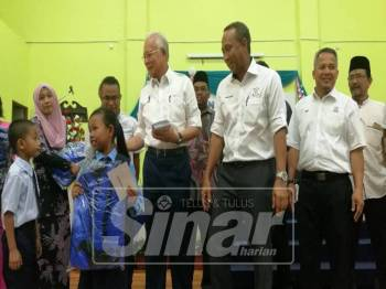 Najib (tiga, kanan) dan Fakhruddin menyampaikan sumbangan kepada 647 murid dari 14 buah sekolah dalam Dun Bebar.