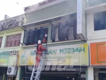 Anggota bomba dan penyelamat sedang memadam kebakaran yang berlaku di rumah kedai tersebut.