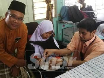 Hasnul Zulkarnain (kanan) menyantuni seorang pelajar Pendidikan Khas SMK Seri Perak menikmati hidangan makanan segera KFC yang disumbangkan pihaknya hari ini.