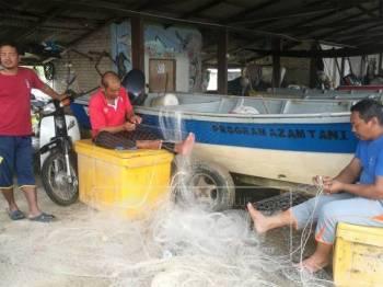 Nelayan mengambil peluang membaiki pukat ketika musim tengkujuh.