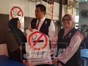 Afif memberi tanda larangan merokok kepada salah seorang pemilik kedai.