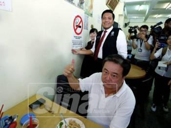 Afif melekatkan papan tanda larangan merokok di salah sebuah kedai.