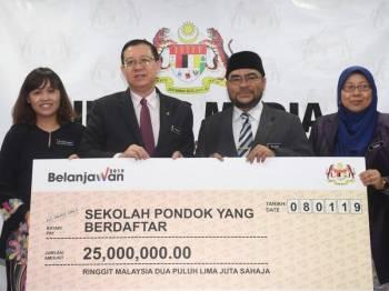 Menteri Kewangan Lim Guan Eng (dua, kiri) menyerahkan peruntukan kepada Menteri di Jabatan Perdana Menteri, Datuk Seri Mujahid Yusof Rawa pada Majlis Penyerahan Cek Kepada Sekolah Pondok Berdaftar di Kementerian Kewangan hari ini. - Foto Bernama