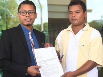 Wakil Orang Asli Pos Lanai, Cameron Highlands Jeffry Hassan (kanan) menyerahkan surat kepada Pegawai Pejabat Peguam Negara Wasri Ahmad Sujani di Jabatan Peguam Negara hari ini berhubung tanah adat mereka yang diceroboh. - Foto Bernama