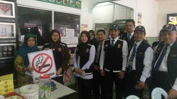 Tuan Jah (dua, kiri) turut bersama pegawai penguat kuasa menyampaikan papan tanda larangan merokok kepada pengusaha premis makanan di Tanah Merah.