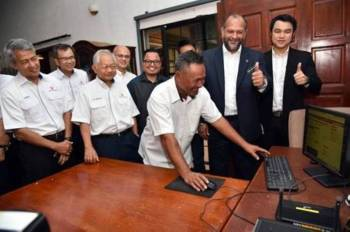 Gobind dan Moggie melihat Pengerusi Majlis Pengurusan Kampung Kampung (MPKK) juga generasi kedua peneroka Felda, Redwan Sentul, 58, melayari internet di rumahnya.