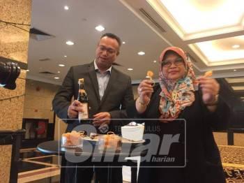 Mohd Nazri (kiri) bersama Hasnah menunjukkan pembukusan terbaharu produk Cap Kipas Udang yang digunakan.5
