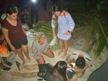 Orang ramai memberi bantuan kecemasan kepada mangsa di Pantai Chenang.