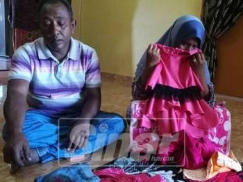 Norhasyelawati mencium pakaian anaknya Nurul Hanim yang dijahit sendiri sambil diperhatikan suaminya