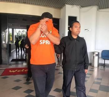 Suspek ketika dibawa keluar dari Mahkamah Majistret Ayer Keroh, tadi.