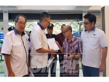 Teik Liang (dua dari kiri) menyerahkan surat bantahan kepada Eng Keat di Komtar tadi.