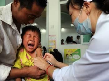 Seorang kanak-kanak menerima suntikan vaksin imunisasi bagi membasmi penyakit polio.