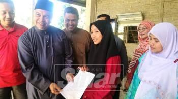 Amiruddin (dua, kiri) melihat surat tawaran kemasukan MRSM diterima Nurul Syafika Mohd Asri di Kampung Seberang Paya Empa.