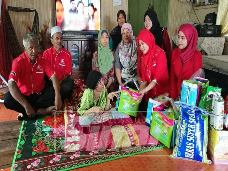 Hidatul Syuhada (dua, kanan) menyerahkan sumbangan lampin pakai buang dan juga keperluan harian kepada Som ketika mengunjungi rumah sewanya di Kampung Tok Adis, Kuala Ibai, di sini. Hadir sama, Ketua Cawangan Bersatu Kuala Ibai, Abdul Wahab Awang (dua kiri).