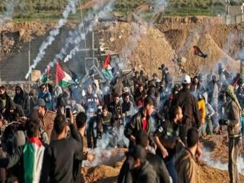 Penduduk Palestin bertempur dengan tentera rejim semasa bantahan di pagar sempadan Gaza-Israel.