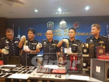 Nik Ros Azhan (tengah) menunjukkan barangan yang dirampas dari kumpulan berkenaan.