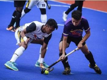 Pemain Maybank Adam Aiman Mamat (kiri) mengasak pemain UiTM Fallah Hassan Shahrom Jamil dalam perlawanan kalah mati Piala Tan Sri P. Alagendra 2019 di Stadium Hoki Nasional Bukit Jalil pada awal Januari. - Foto Bernama