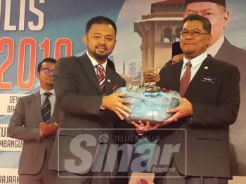 Mohd Radzi (kiri) menyampaikan cenderahati kepada Dzulkefly (kanan).