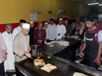 Sultan Abdullah turut mencuba memasak roti canai sambil disaksikam sendiri penebar roti di Restoran D'Wafi, Taman Mahkota Putra, di sini, hari ini.