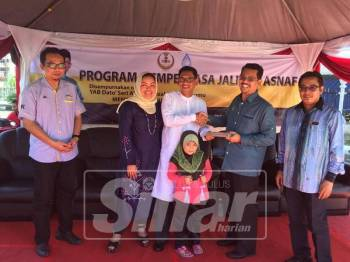 Ahmad Faizal (tengah) menyerahkan sumbangan zakat LAP untuk diagihkan kepada golongan asnaf pada Program Memperkasa Jalinan Asnaf di sini.