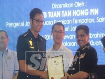 Azmi (kanan) menyerahkan sijil penghargaan kepada kakitangan MPK sambil diperhatikan Hong Pin (tengah).