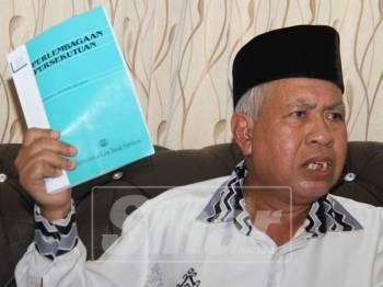 Sallehuddin bersama buku Perlembagaan yang turut menjadi asas dan intipati perjuangannya dalam PRK tersebut.