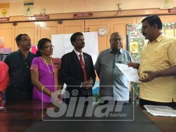 Ramakrishnan mendengar penerangan wakil kontraktor SJKT Ladang Tebrau sebelum menyerahkan CCC.