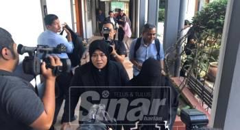 Tertuduh (kanan) berpurdah keluar dari mahkamah dikawal anggota SPRM selepas tidak mengaku ke atas semua tuduhan itu.