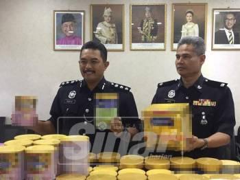 Mohd Ali (kiri) menunjukkan pelbagai jenama susu yang dicuri wanita dan anak serta adik lelakinya yang ditahan polis.