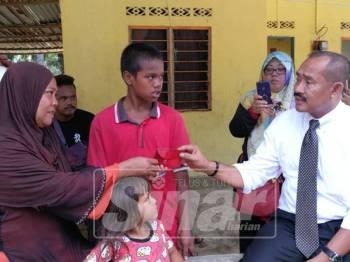 Abu Bakar (kanan) memberi sumbangan kepada ibu tunggal, Rosnah Samad di rumahnya.