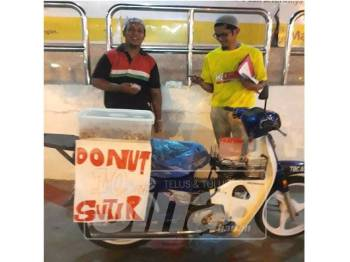 Idham Syafiq (kiri) bersama seorang pelanggan di sekitar bandar Kuala Terengganu.