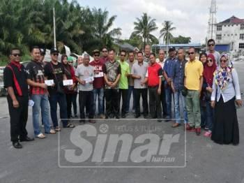 Peniaga Downtown Parit Raja sewaktu menerima wang sumbangan Ahli Parlimen Sri Gading, Dr Shahruddin Md Salleh.