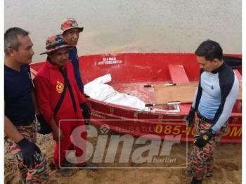 Anggota bomba menaikkan mayat mangsa dan diserahkan kepada polis di tebing Sungai Besut dekat Kampung Tok Raja di seberang kampung Dengir pagi ini.