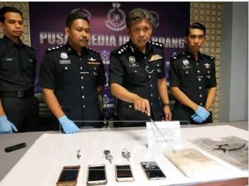 Ismadi (dua dari kanan) menunjukkan dadah dan barang yang dirampas dalam serbuan kelmarin
