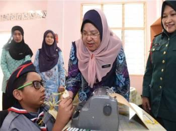 Pengarah Bahagian Pendidikan Khas Kementerian Pendidikan, Datuk Dr Yasmin Hussain melihat adik Muhammad Afiq Darwish Mohd Adnan yang cacat penglihatan mengendalikan mesin braille semasa melakukan lawatan sempena 'Penanda Aras Pelaksanaan Zero Reject Policy' bagi murid berkeperluan khas 2019 di SMK Putrajaya Presint 18(1). Turut sama Pengetua SMK Presint 18 (1), Datin Haliza Hussin (kanan). - Foto Bernama