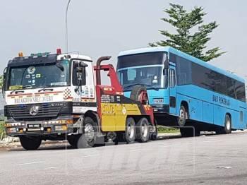 Bas kilang yang ditunda selepas memarkir kenderaan berat di tempat yang tidak dibenarkan.
