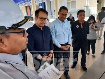 Chee Keong (dua, kiri) dan Mohd Asmirul (tiga, kiri) mendengar taklimat berkaitan pembinaan pusat latihan skuasy.