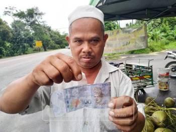 Jaafar menunjukkan sekeping wang palsu bernilai RM100 daripada pelanggannya yang membeli dua gelas air kelapa.