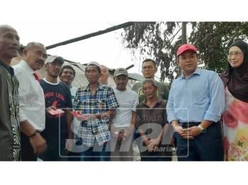 Abu Bakar Yahya (dua dari kiri) dan  Datuk Dr. Md Farid Md. Rafik (dua dari kanan) menyampaikan sumbangan kepada mangsa kebakaran di Jalan Terminal Bas Lama, Pontian, Johor hari ini.