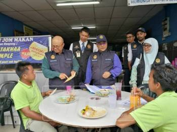Dr Sha'ari (berdiri, kiri) mengedarkan risalah larangan merokok di kawasan premis kedai kepada orang awam ketika mengadakan melakukan pemeriksaan di premis makanan di sekitar Kuantan di sini, hari ini.