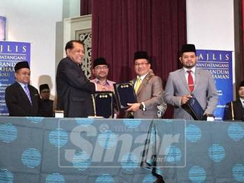 Mujahid (tengah) menyaksikan pertukaran dokumen perjanjian antara Picoms dan Jawi.