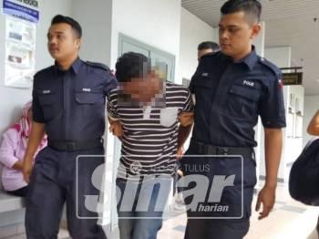 Tertuduh ketika dibawa keluar dari Mahkamah Majistret Ayer Keroh, di sini, hari ini.