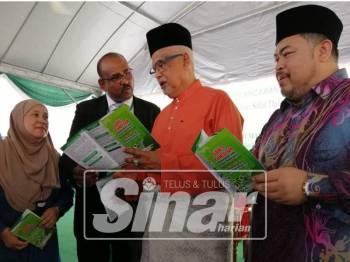 Mahfuz (dua, kanan) melihat risalah Garis Panduan Menunaikan Solat Dalam Waktu Kerja yang diterbitkan, hari ini.