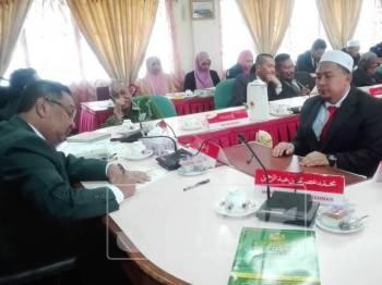 Tengku Azmi (kiri) menandatangani watikah pelantikan 22 ahli MDK-PI, semalam.